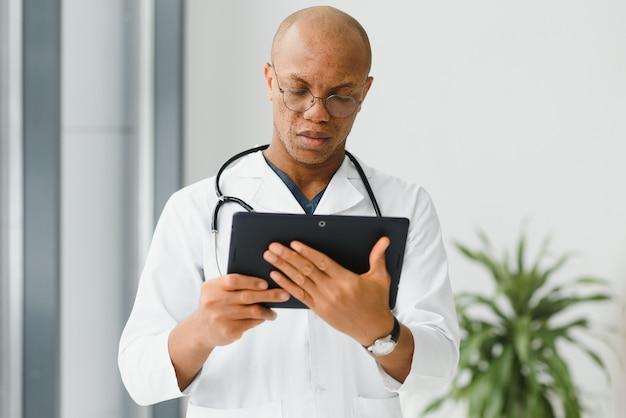 Médico africano maduro usando tablet digital no corredor.