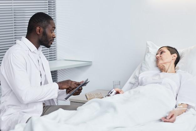 Médico africano prescrevendo um medicamento para uma mulher madura enquanto ela estava deitada na cama no hospital