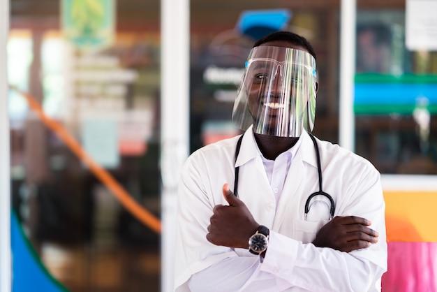Médico africano usar escudo facial e segurando o estetoscópio com mostrar bom sinal