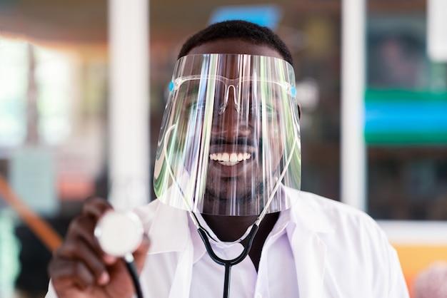 Médico africano usar escudo facial e segurando o estetoscópio com tipo e sorrindo