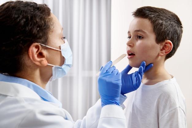 Médico afro-americano com máscara facial e luvas protetoras, examinando a garganta do menino caucasiano durante uma visita domiciliar.
