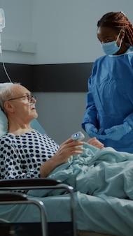 Médico afro-americano conversando com paciente com doença