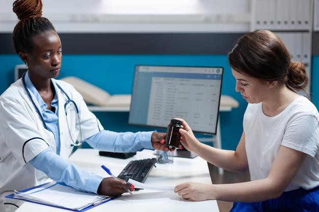 Médico afro-americano dando prescrição de antibióticos ao paciente
