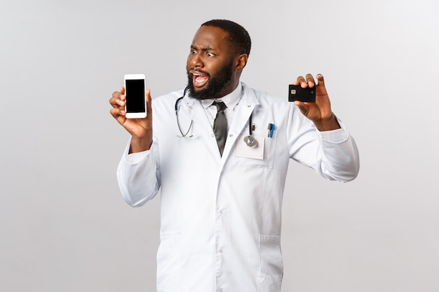 Médico afro-americano de retrato em uniforme branco.