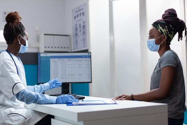 Médico afro-americano discutindo com paciente doente