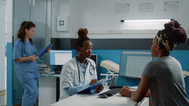 Médico afro-americano e paciente fazendo consulta