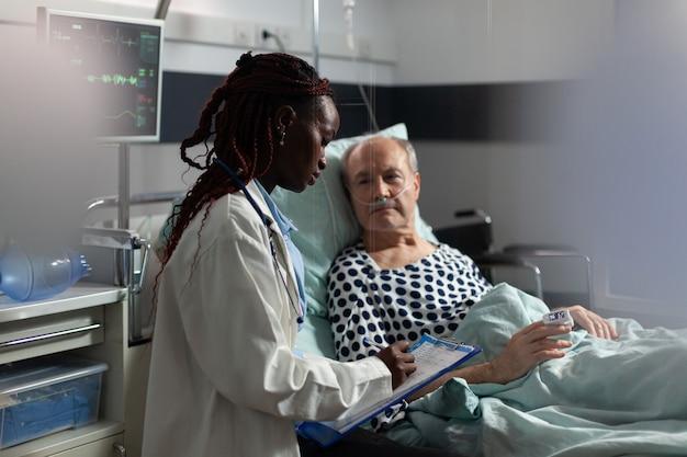 Médico afro-americano em quarto de hospital, discutindo diagnóstico e tratamento com homem idoso doente leigos.