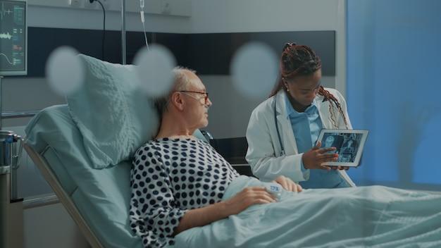 Médico afro-americano explicando o raio-x em tablet ao paciente