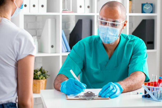 Médico afro-americano fazendo anotações na prancheta enquanto está sentado à mesa