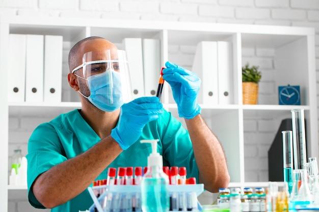 Médico afro-americano ou trabalhador de laboratório examina amostra de sangue na clínica
