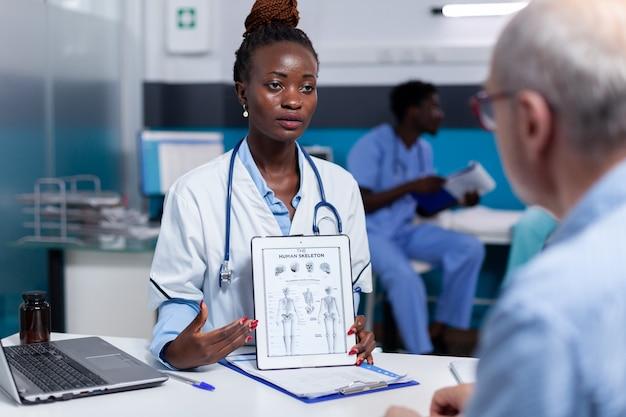 Médico afro-americano segurando ilustração na tela do tablet