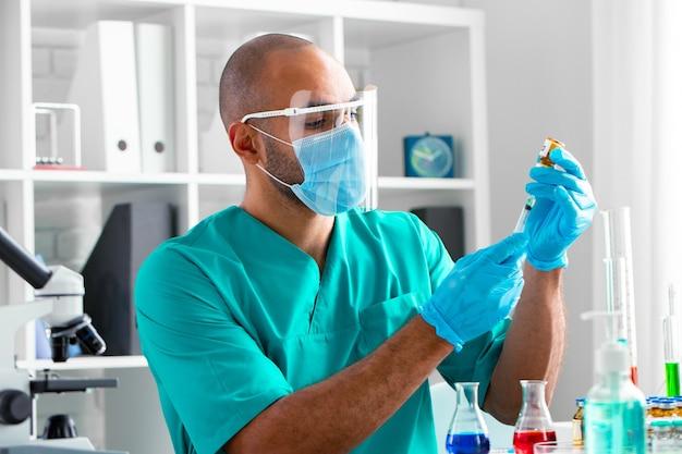 Médico afro-americano sentado à mesa e se preparando para aplicar uma injeção de droga, retrato