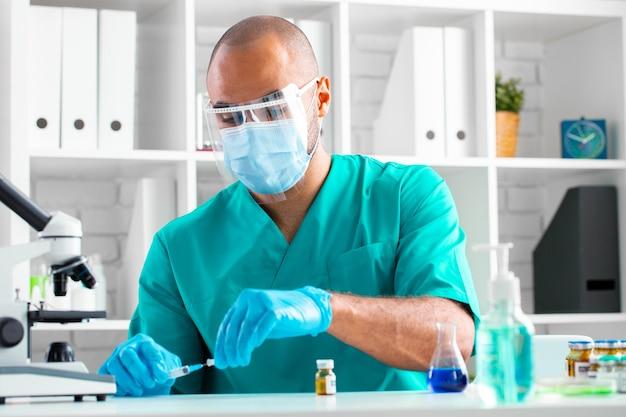 Médico afro-americano sentado à mesa e se preparando para injetar um medicamento