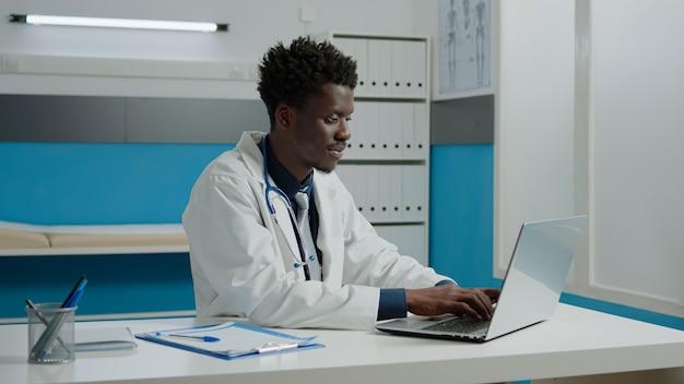 Médico afro-americano usando laptop enquanto está sentado na mesa no quarto de hospital. especialista em saúde negro trabalhando com tecnologia para consulta em gabinete moderno em instalação médica