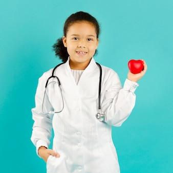 Médico afroamerican bonito que guarda o coração
