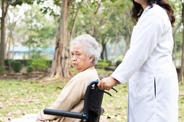 Médico, ajuda e atendimento paciente asiático sênior mulher sentada na cadeira de rodas no parque.
