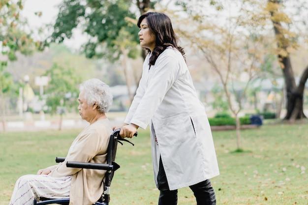Médico ajuda e cuida de uma paciente asiática idosa sentada em uma cadeira de rodas no parque