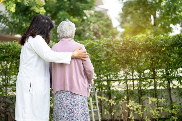 Médico, ajuda e cuidado mulher idosa asiática sênior ou idosa usar o andador com forte saúde enquanto caminhava no parque em um feliz feriado fresco.