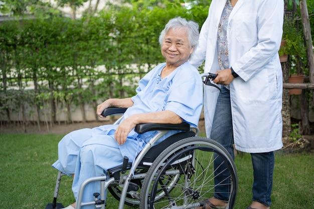 Médico, ajuda e cuidado paciente asiático sênior ou idosa senhora idosa sentado na cadeira de rodas no parque na enfermaria do hospital de enfermagem, conceito médico forte e saudável.