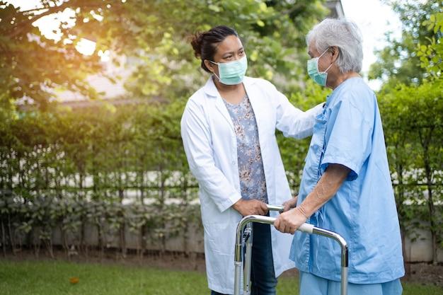 Médico, ajuda e cuidados, mulher asiática idosa usa andador com forte saúde ao caminhar no parque