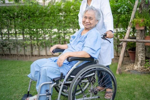 Médico, ajuda e cuidados, paciente asiática idosa sentada em uma cadeira de rodas no parque