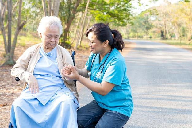 Médico, ajuda e cuidados paciente asiático sênior mulher sentada na cadeira de rodas no parque.