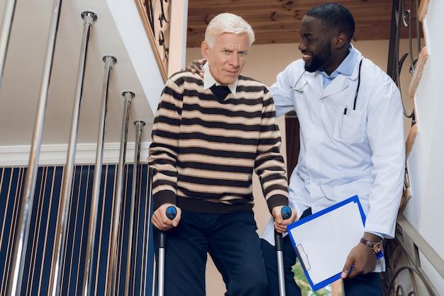 Médico ajuda um homem a descer as escadas em um lar de idosos.