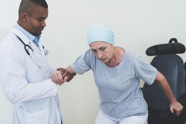 Médico ajuda uma mulher que se submetem a reabilitação