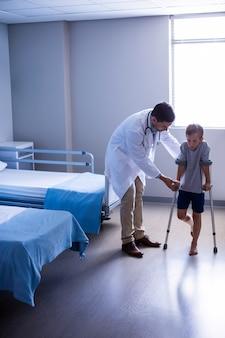 Médico, ajudando o menino ferido a andar com muletas