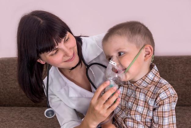 Médico ajudando o pequeno paciente a colocar uma máscara para inalação