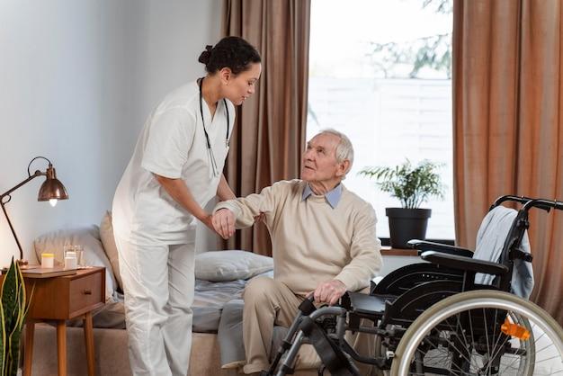 Médico ajudando paciente idoso