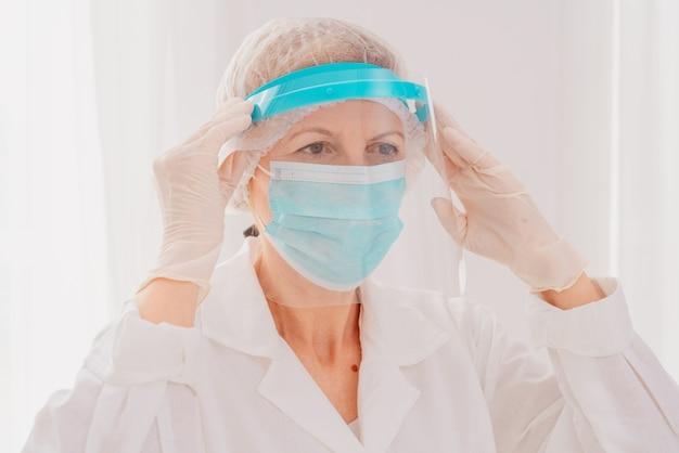 Médico ajusta a tela do protetor facial contra vírus secreto