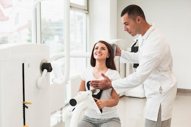 Médico, ajustando a cabeça do paciente na máquina médica