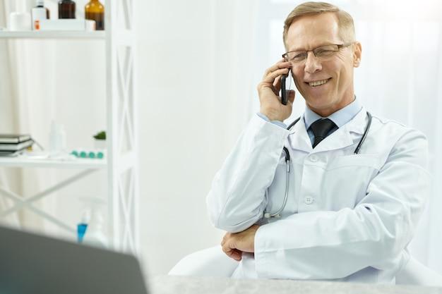 Médico alegre conversando ao telefone na clínica