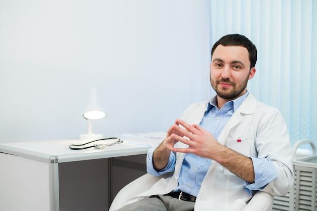 Médico alegre conversando e olhando. médico em conversa com o paciente enquanto está sentado no hospital.