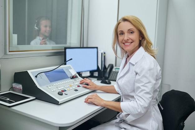 Médico alegre de meia-idade fazendo um teste de audiometria