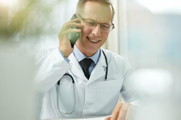 Médico alegre falando no celular na clínica