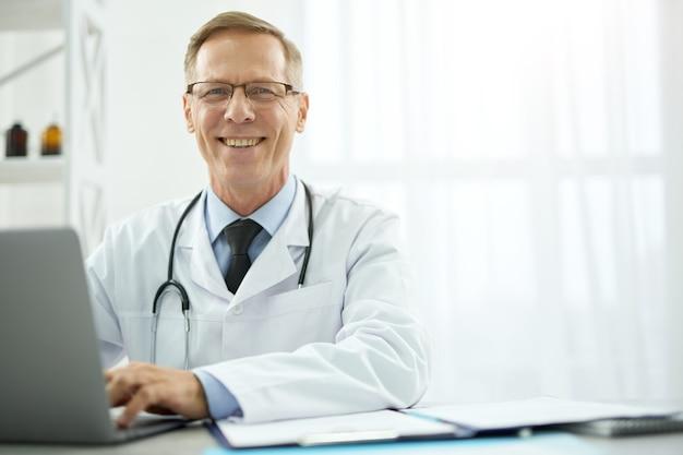 Médico alegre sentado à mesa com o laptop na clínica
