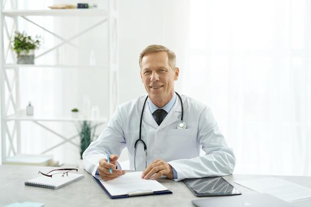 Médico alegre sentado à mesa na clínica