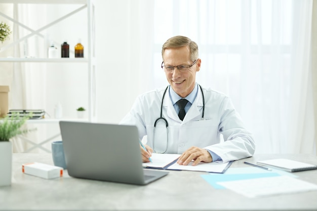 Médico alegre usando laptop e preenchendo o prontuário do paciente
