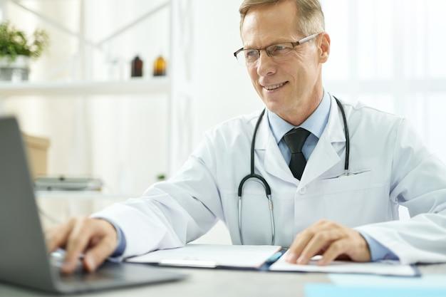 Médico alegre usando notebook moderno na clínica