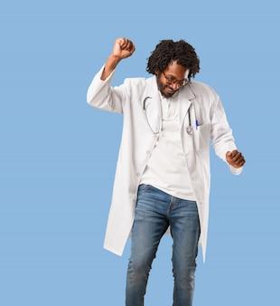 Médico americano africano bonito ouvindo música, dançando e se divertindo