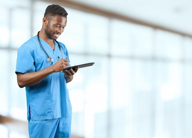 Médico americano africano com um pé de estetoscópio contra turva