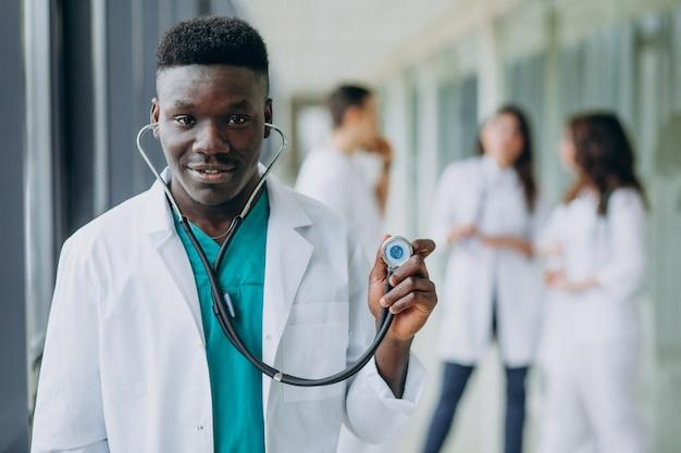 Médico americano africano homem com estetoscópio, em pé no corredor do hospital