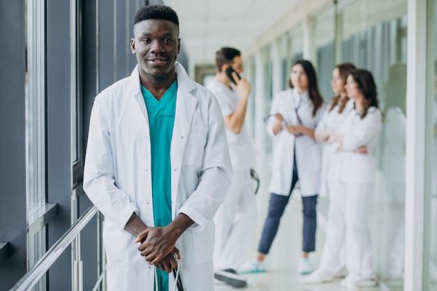 Médico americano africano homem de pé no corredor do hospital