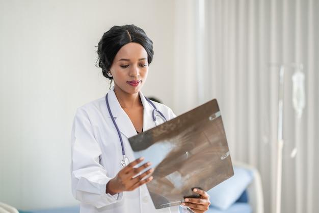 Médico americano africano mulher olhando radiografia de raio-x no quarto do paciente