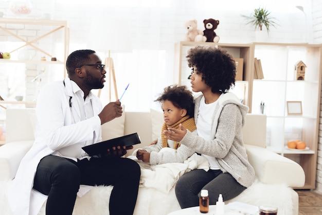 Médico americano explicando a mãe com uma criança doente.