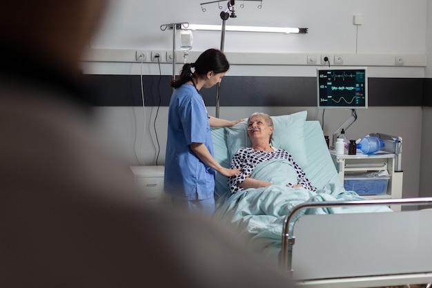 Médico amigável com as mãos segurando a mão do paciente, no quarto de hospital, dando encorajamento, empatia e apoio durante o exame médico