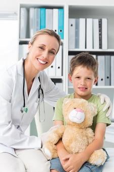 Médico amigável com menino segurando ursinho de pelúcia