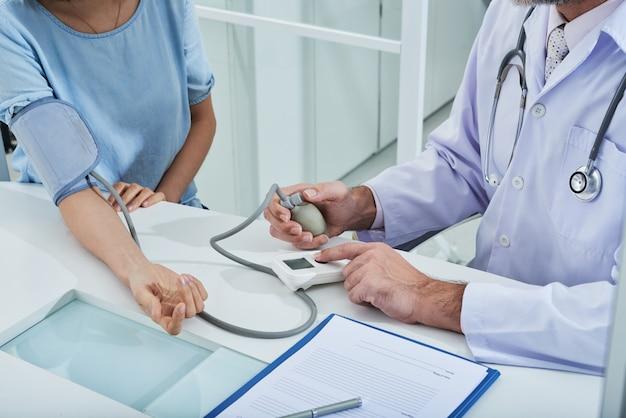 Médico anônimo que mede a pressão arterial de um paciente irreconhecível com um tonômetro